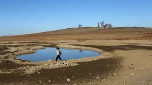 A visitor walks near the receding waters at Folsom Lake, which is 17 percent of its capacity, in Folsom, California January 22, 2014. California Governor Jerry Brown last week declared a drought emergency, and the dry year of 2013 has left fresh water reservoirs with a fraction of their normal water reserves. Picture taken January 22, 2014. REUTERS/Robert Galbraith (UNITED STATES - Tags: ENVIRONMENT TPX IMAGES OF THE DAY) - RTX17T4L