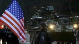 """A soldier of the U.S. Army waves as he arrives in the Czech Republic during the """"Dragoon Ride"""" military exercise in Harrachov March 29, 2015. The """"Dragoon Ride"""" military exercise involves soldiers of the U.S. Army-Europe's 2nd Cavalry Regiment, deployed in Estonia as a part of the Operation Atlantic Resolve, moving along a 1800 km-long route across Latvia, the Czech Republic and Germany, where they will re-base at the Rose Barracks, in the north-east Bavarian town of Vilseck. REUTERS/David W Cerny - RTR4VDFV"""